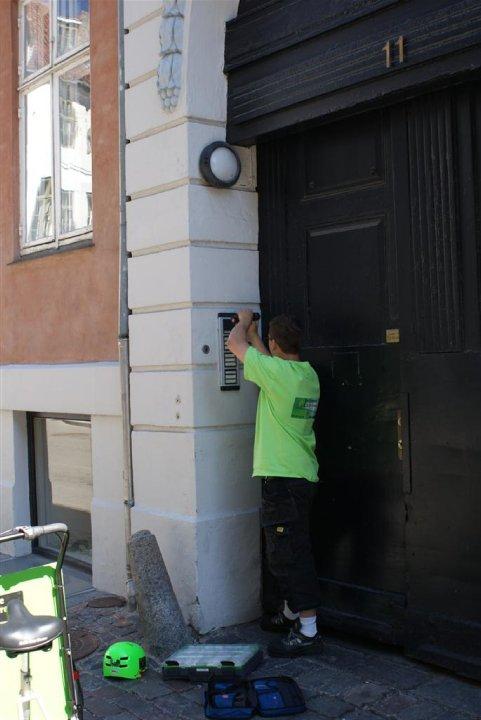 Elektriker installerer dørtelefon ved siden af ladcykel i København