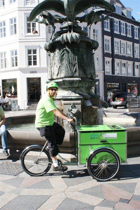 En Grøn Elektriker på en elcykel i København ved springvand