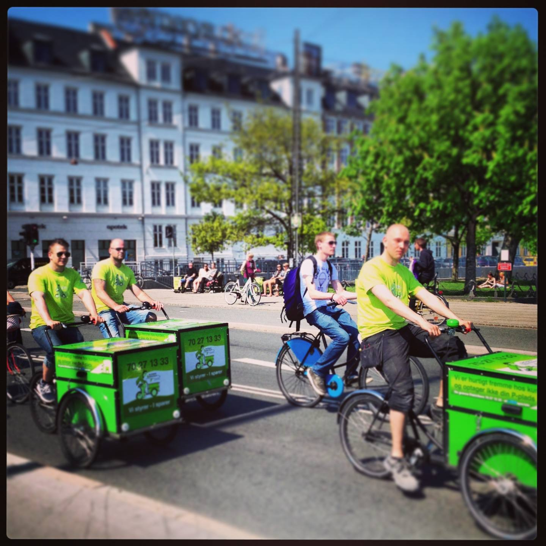 Elektrikere cykler på grønne ladcykler ved søerne i København